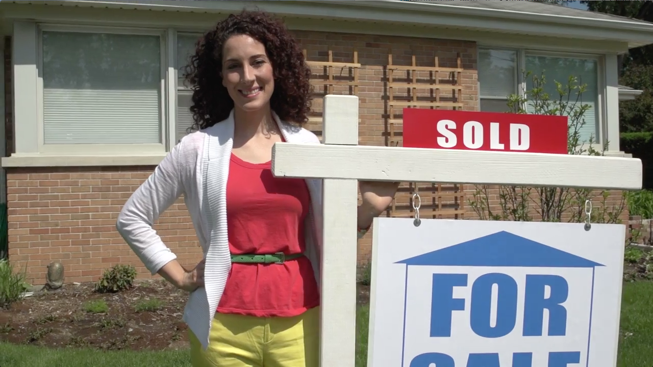Real Estate Agent Next to For Sale Sign
